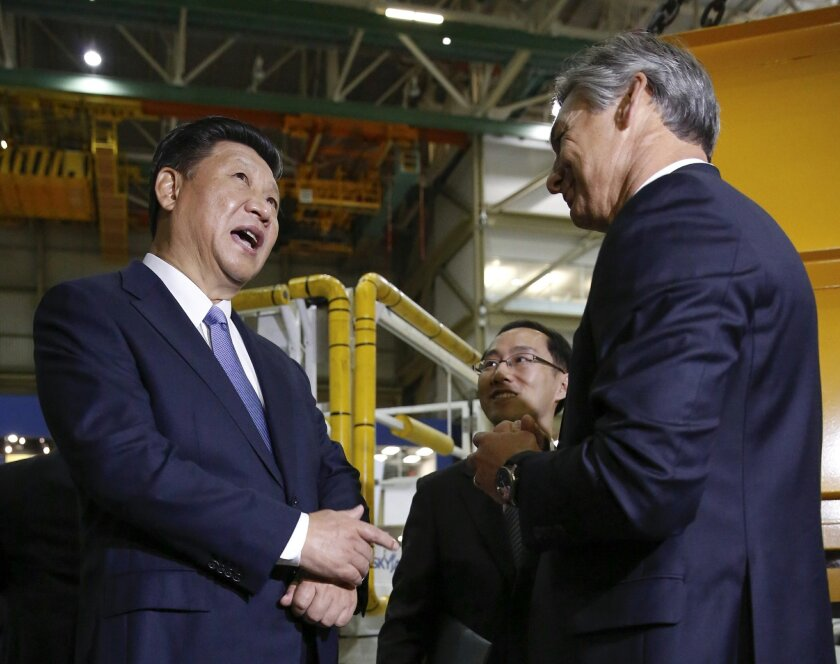 Chinese President Xi Jinping, left, and president and CEO Boeing Commercial Airplanes, Ray Conner, talk while touring the Boeing assembly line, Wednesday, Sept. 23, 2015, in Everett, Wash. Boeing has agreed to buy about 300 jets from Boeing. In addition, state-owned Commercial Aircraft Corp. of China signed a cooperation agreement with the aerospace giant to build a 737 aircraft assembly center in China. (Jason Redmond/Pool Photo via AP)