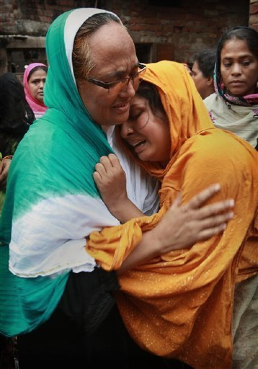 Relatives mourn the death of a victim of a fire in Dhaka, Bangladesh, Friday, June 4, 2010. A devastating fire raced through several apartment complexes in the Bangladeshi capital Thursday, killing and injuring scores of people. (AP Photo/Pavel Rahman)