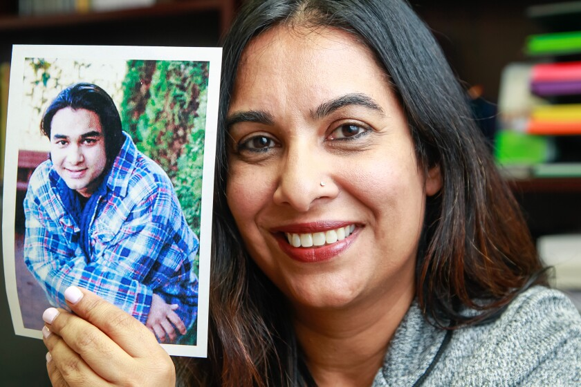 SAN DIEGO, CA December 6th, 2018 | Tasreen Khamisa (right), executive director of the Tariq Khamisa Foundation, holds a picture of her brother Tariq in 2018 at the company's offices in San Diego, California. Her brother, Tariq, was killed by Tony Hicks in 1995.
