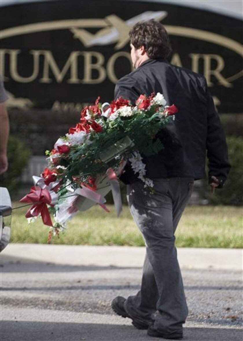 A florist delivery worker carries a wreath of flowers at the entrance to Jumbolair Aviation Estates, where actor John Travolta and his family have a home Wednesday, Jan. 7, 2009  near Ocala, Fla. Friends and relatives are expected for a ceremony Thursday to be held for the death of the Travolta's s