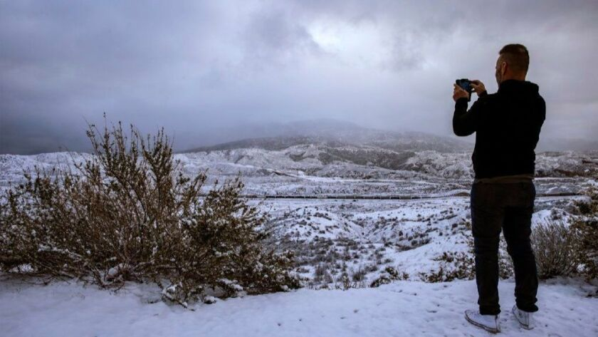 Greg Hunkle, 55, takes a picture last month at Cajon Summit on his way to Las Vegas. On Tuesday night, a new low pressure system could mean up to 4 inches of snow along the Grapevine stretch of the 5 Freeway.
