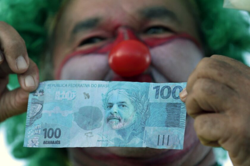 A clown dressed demonstrator holds up a replica of a 100 Brazilian real note decorated with an image of former President Luiz Inacio Lula da Silva, during protest calling for the impeachment of Brazil's President Dilma Rousseff and against the naming of her mentor, Lula da Silva, as her new chief of staff, outside Planalto presidential palace in Brasilia, Brazil, Monday, March 21, 2016. Supporters say the move will help the president fight impeachment proceedings and critics blast it as a scheme to shield Lula from possible detention in corruption probes related to a bribery scandal at Brazil's state oil company Petrobras. (AP Photo/Eraldo Peres)