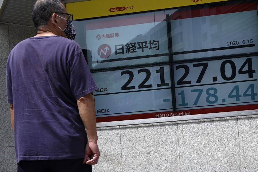 A man looks at an electronic stock board showing Japan's Nikkei 225 index at a securities firm in Tokyo Monday, June 15, 2020. Asian shares were mostly lower Monday on concern over a resurgence of coronavirus cases and pessimism after Wall Street posted its worst week in nearly three months. (AP Photo/Eugene Hoshiko)