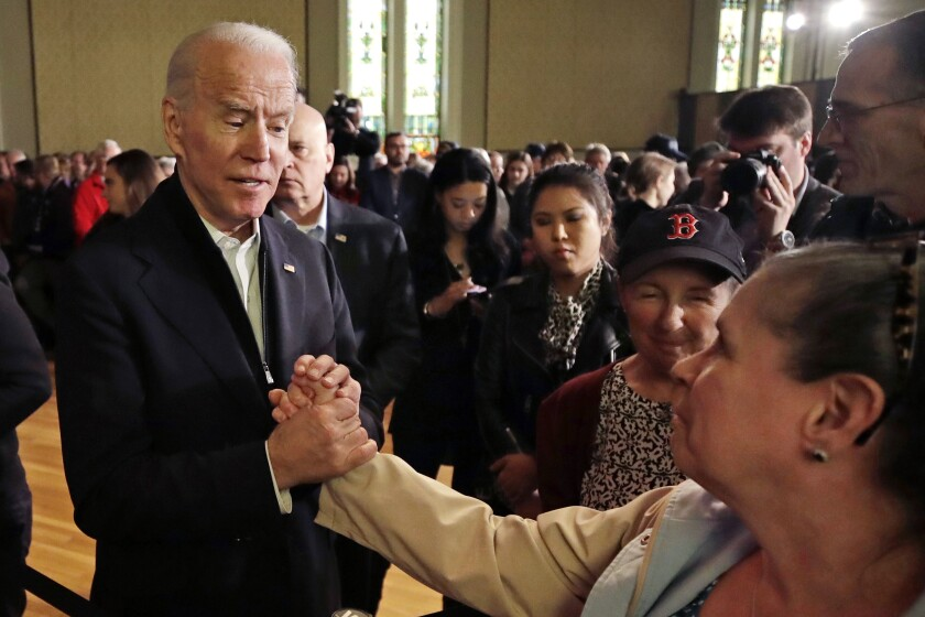 Democratic presidential candidate former Vice President Joe Biden holds a woman's hand while speaking to her at a campaign event, Wednesday, Feb. 5, 2020, in Somersworth, N.H. (AP Photo/Elise Amendola)
