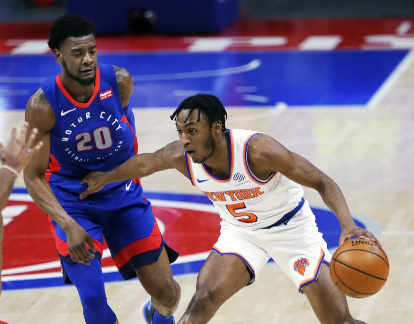 New York Knicks guard Immanuel Quickley (5) holds off Detroit Pistons guard Josh Jackson (20) during the first half of an NBA basketball game Saturday, April 3, 2021, in Detroit. (AP Photo/Duane Burleson)