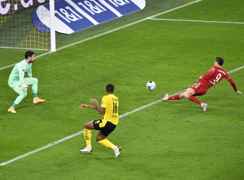 Bayern's Robert Lewandowski scores a goal that was disallowed for offside during the German Bundesliga soccer match between Borussia Dortmund and Bayern Munich in Dortmund, Germany, Saturday, Nov. 7, 2020. (AP Photo/Martin Meissner, Pool)