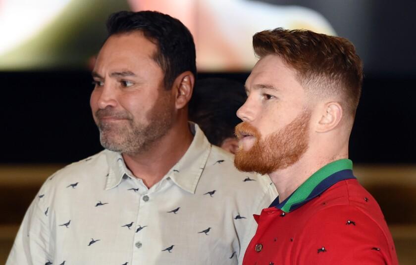 Oscar De La Hoya, left, says everything is fine between him and Canelo Alvarez.