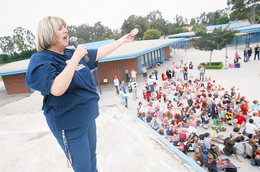 """Principal Charlene Metoyer performs a """"donut salute"""" to her sixth-grade class while standing atop the roof at Eastbluff Elementary School in 2006. Metoyer has announced she's running for school board."""