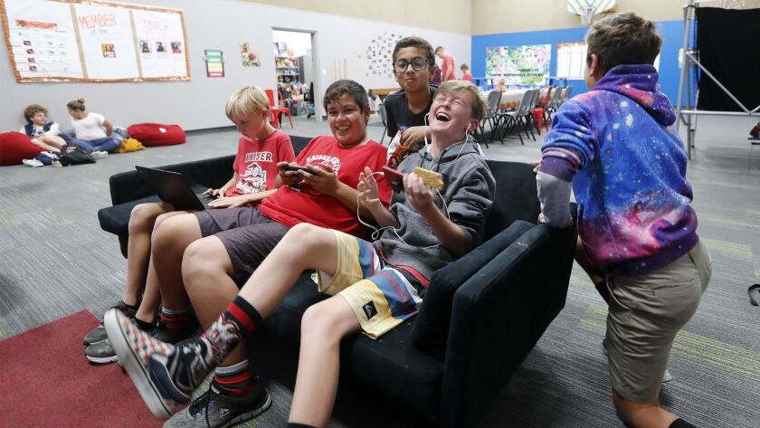 Teens enjoy themselves in the Teen Center room as they play video games at the Boys & Girls Club of