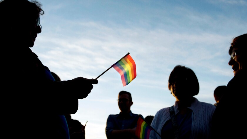 The setting sun illuminates a gay pride flag held by Dina Doerfer of Millcreek Township as she attends a vigil in Erie, Pa.