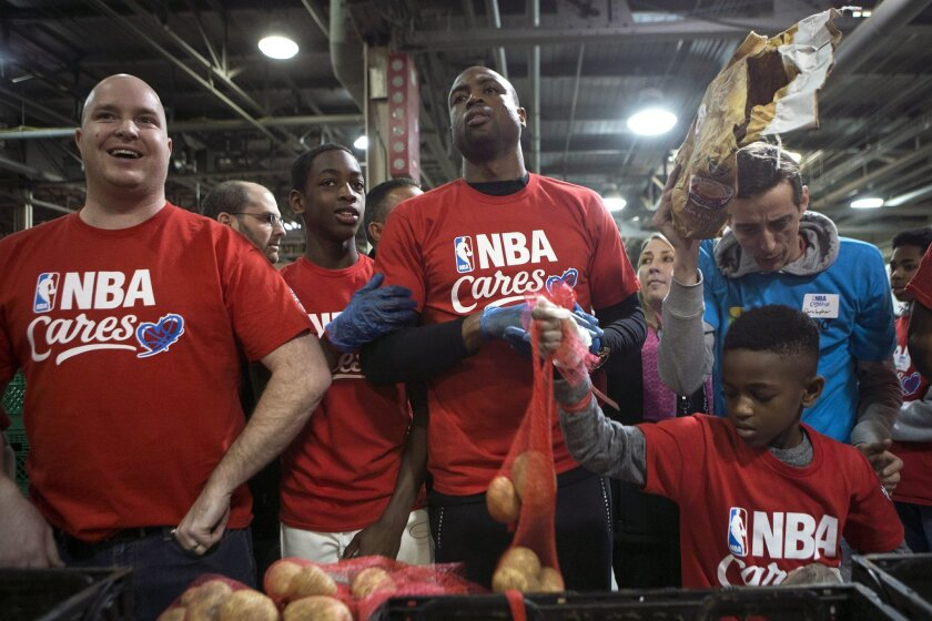 Miami Heat's Dwyane Wade, center, helps sort food donations for The Daily Bread Food Bank in Toronto, Friday, Feb. 12, 2016. (Chris Young/The Canadian Press via AP) MANDATORY CREDIT