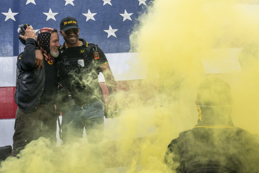 Two men in front of yellow fog and an American flag