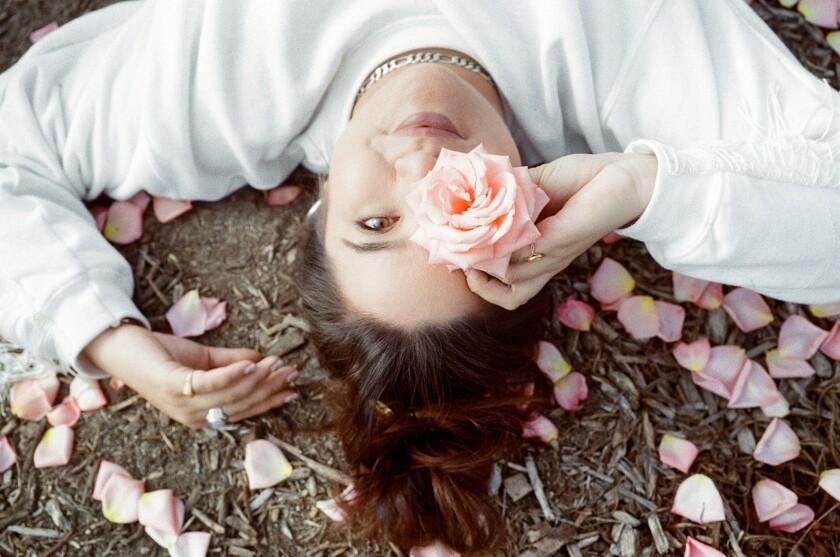 Floral designer Alex Floro poses with a rose.