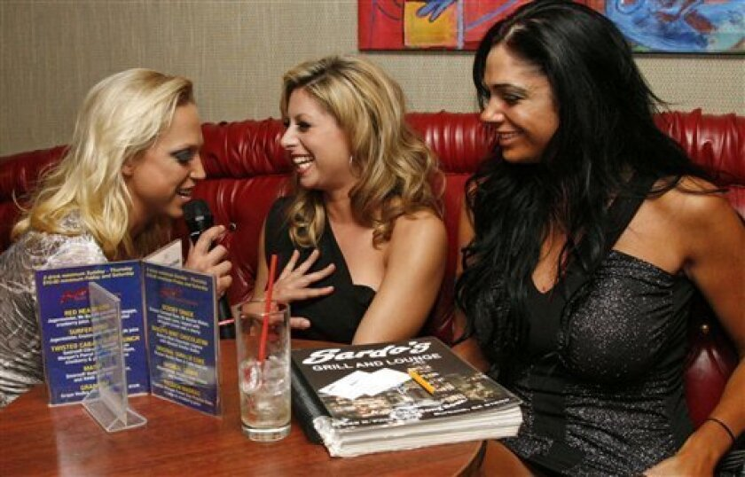From left, adult entertainer and hostess Nicki Hunter flirts with adult entertainers Suzanne Schevelle and Angela Aspen in the audience during Porn Star Karaoke at Sardo's Grill and Lounge in Burbank, Calif. on Tuesday, Nov. 17, 2009. (AP Photo/Jason Redmond)