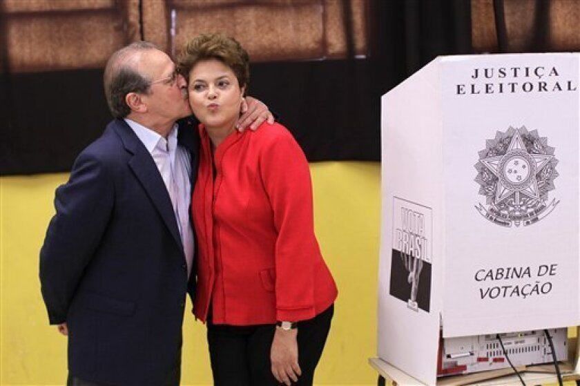 Dilma Rousseff, presidential candidate for the Workers Party, right, is kissed by Tarso Genro, candidate for Governor of Rio Grande do Sul, next to an electronic ballot box after voting in Porto Alegre, Brazil, Sunday, Oct. 3, 2010. Brazilians vote Sunday in national elections that could see front-running candidate Dilma Rousseff become the country's first female president, succeeding her popular ally and mentor, Brazil's President Luiz Inacio Lula da Silva. (AP Photo/Felipe Dana)