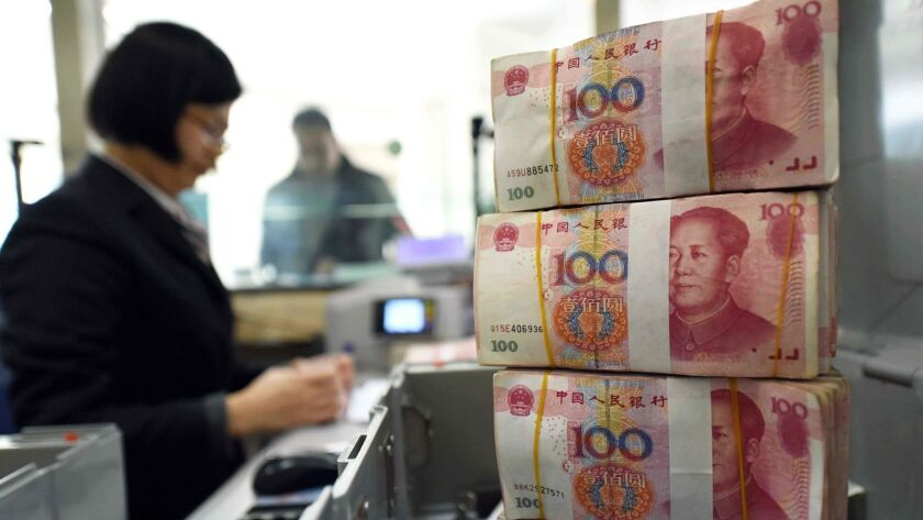 An employee counts money at a bank in Lianyungang, in eastern China's Jiangsu province. In the event of a trade war with the United States, China could resort to devaluing its currency.