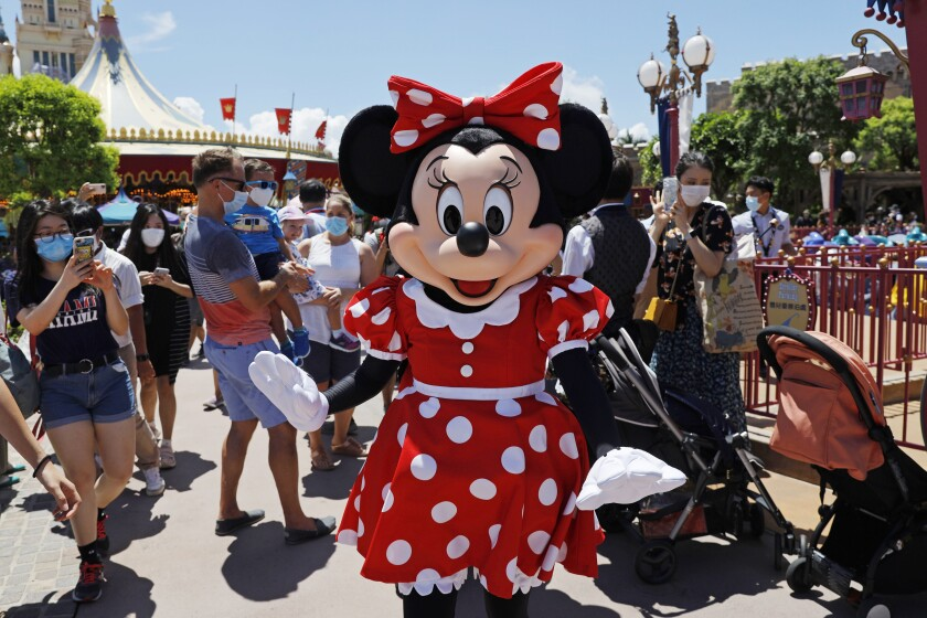 El icónico personaje de Minnie Mouse saluda a los visitantes en el parque Disneyland de Hong Kong en su reapertura en casi cinco meses por la crisis del coronavirus, el 18 de junio de 2020. (AP Foto/Kin Cheung)