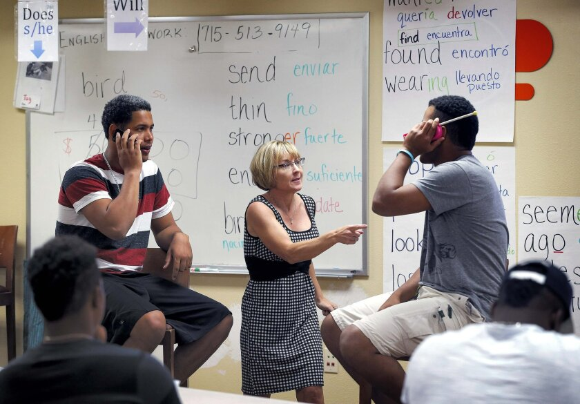 In this May 22, 2014 photo, ESL instructor Carol Gabb, center, helps San Francisco Giants baseball prospects Jose Murel, left, and Reimy Rodriguez converse, in English, on a pretend phone conversation in Scottsdale, Ariz. San Francisco is just one of many clubs putting a stronger emphasis on teachi