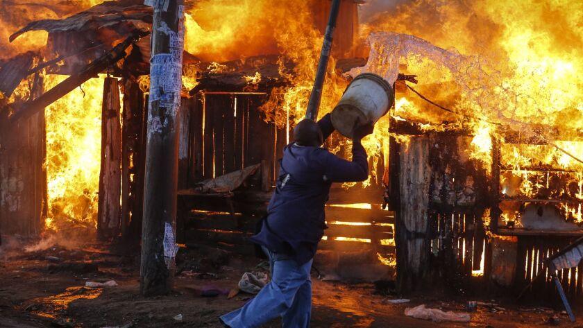 A fire engulfs a market in Kawangware, a neighborhood in western Nairobi, on Oct. 27. The shop, believed to be owned by a member of President Uhuru Kenyatta's Kikuyu tribe, was set ablaze by opposition members of a rival clan.