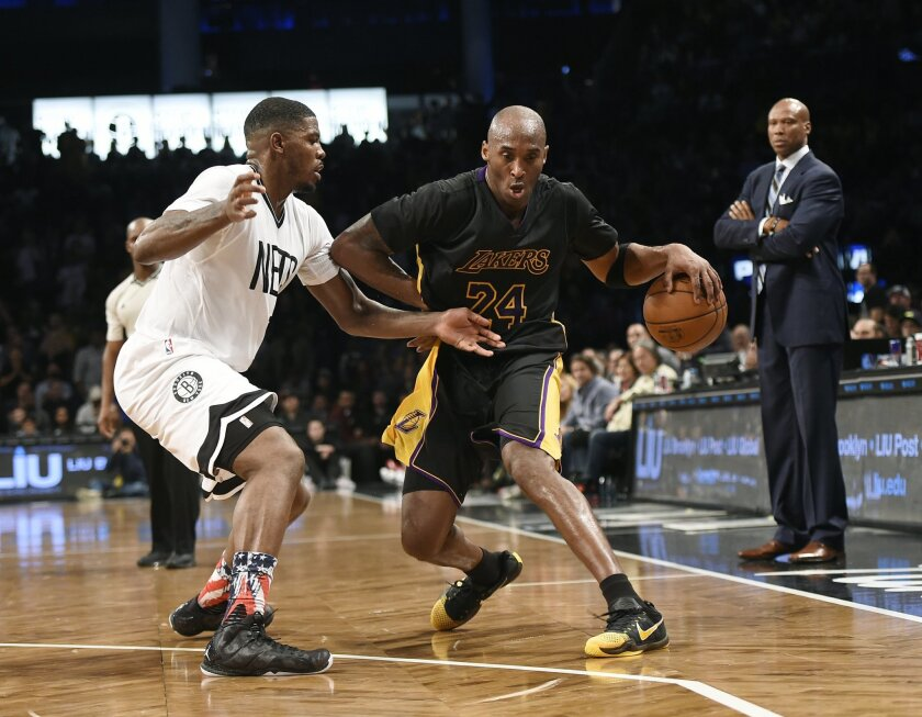 Los Angeles Lakers forward Kobe Bryant (24) drives the ball around Brooklyn Nets forward Joe Johnson as Lakers coach Byron Scott watches at right during the first half of an NBA basketball game Friday, Nov. 6, 2015, in New York. (AP Photo/Kathy Kmonicek)