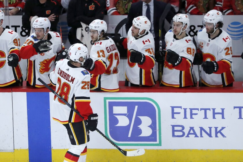 Calgary Flames' Elias Lindholm (28) celebrate his goal with teammates during the second period of an NHL hockey game against the Chicago Blackhawks on Tuesday, Jan. 7, 2020, in Chicago. (AP Photo/Charles Rex Arbogast)