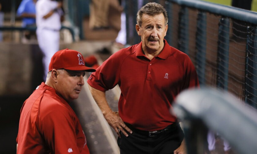 Angels Owner Arte Moreno, right, speaks with Manager Mike Scioscia before a 2012 game. The Angels could opt out of their Angel Stadium lease in October 2016.