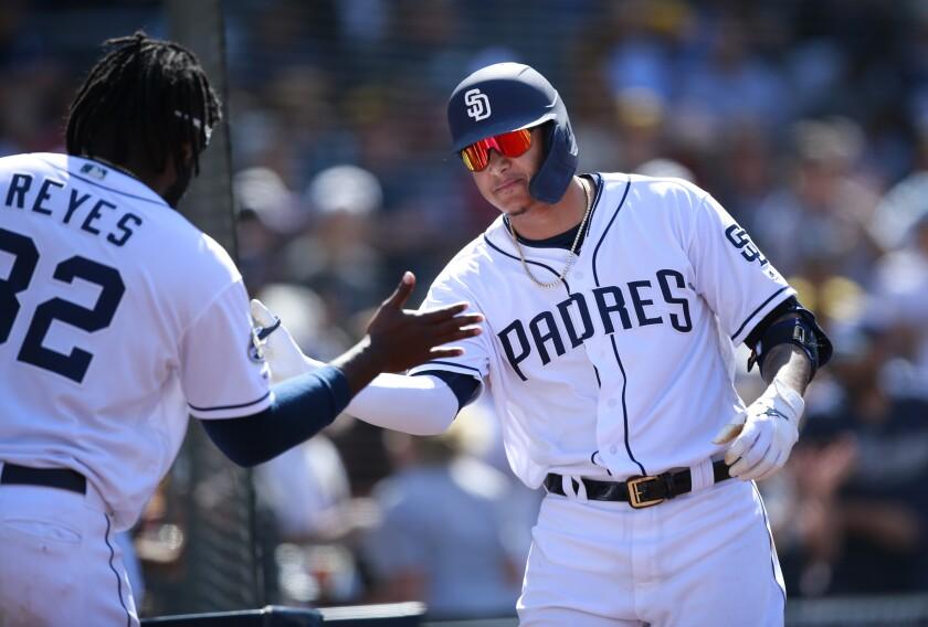Padres' Manny Machado celebrates his two-run home run with Franmil Reyes on Wednesday against the Arizona Diamondbacks at Petco Park.