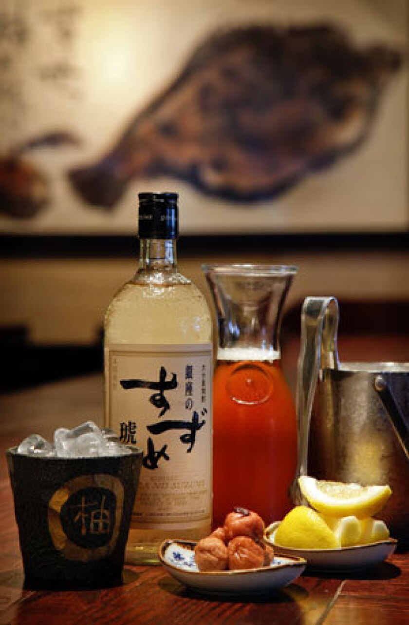 A Ginza No Suzume Kohaku shochu bottle and a carafe of oolong tea, pickled plums and lemon wedges on the counter at Yuzu Izakaya in Torrance.