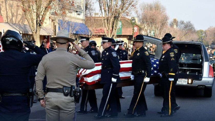 Law enforcement officials carry the casket of police Cpl. Ronil Singh into the Westside Theatre for a public viewing in Newman, Calif.