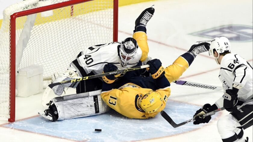 Nashville Predators center Nick Bonino (13) collides with Los Angeles Kings goaltender Calvin Peters
