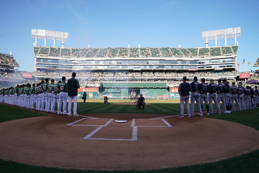 The Oakland Athletics and the Tampa Bay Rays stand during the national anthem prior to the American League wild-card game Oct. 2 at RingCentral Coliseum.