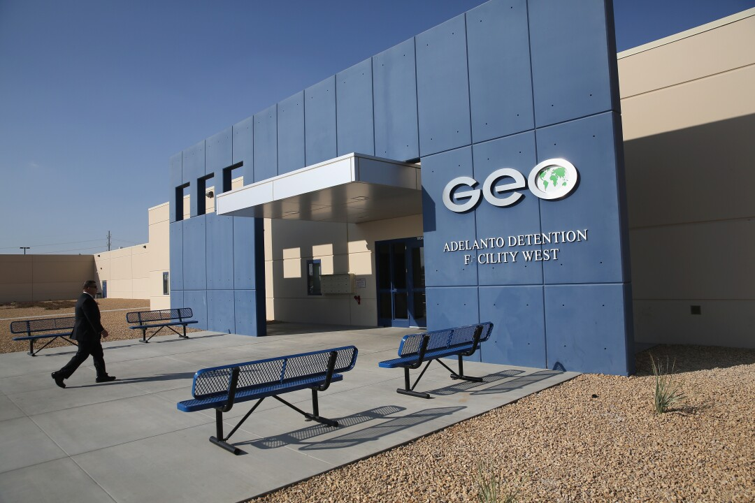 A man walks into a building with a sign that says Geo Adelanto Detention Facility West