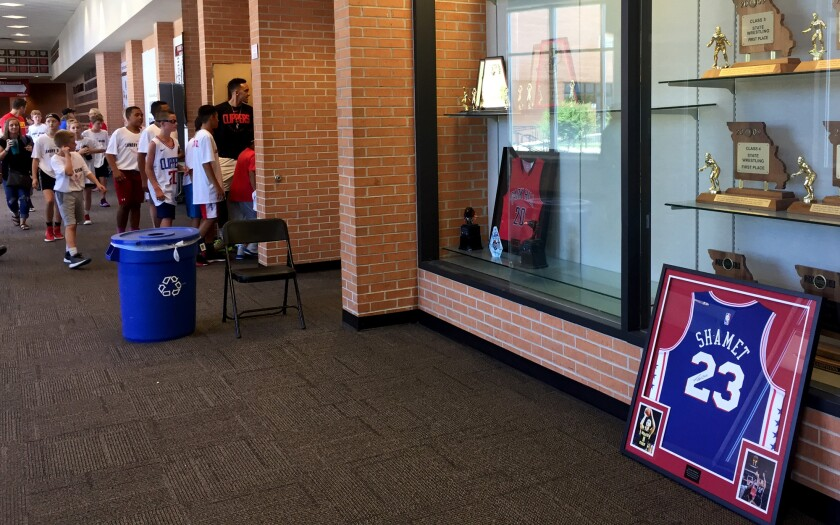 Landry Shamet's framed Clippers jersey sits in front of the Park Hill High trophy case as kids file into the gym for his basketball camp.