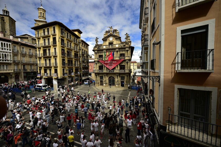 Residents in white clothes and traditional red scarves take to the streets of Pamplona, Spain -- with nary a bull in sight.