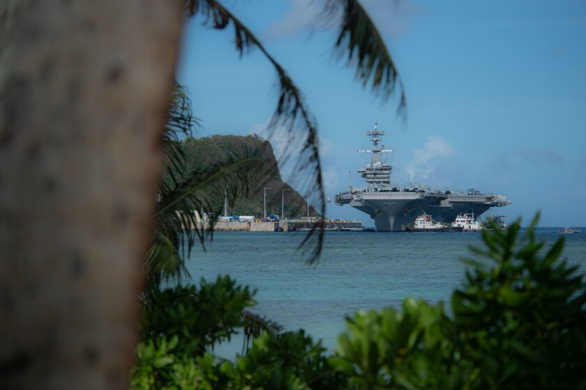 The aircraft carrier Theodore Roosevelt prepares to moor in Guam in 2019. The ship has returned to Guam after several sailors tested positive for COVID-19.