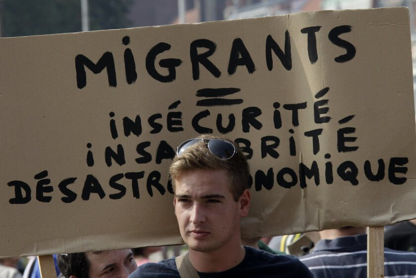 "A man hold a banner which reads ""Migrants equal insecurity, unhealthiness and economic disaster"" in Calais, northern France, Sunday, Sept 7, 2014. Hundreds of extreme-right activists demonstrated Sunday to ""save"" Calais from homeless migrants inundating the French port city in hopes of crossing the English Channel to Britain. (AP Photo/Michel Spingler)"