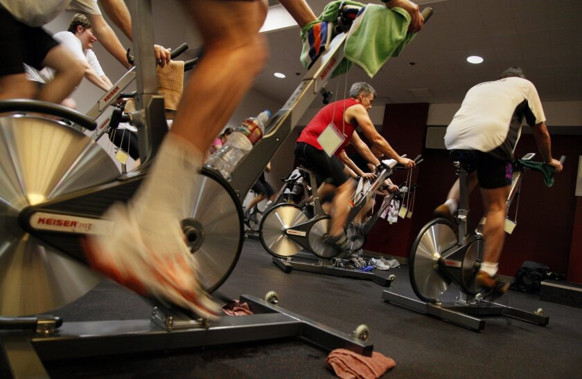 Exercisers crank up the energy at an indoor cycling class at the Mission Valley YMCA.