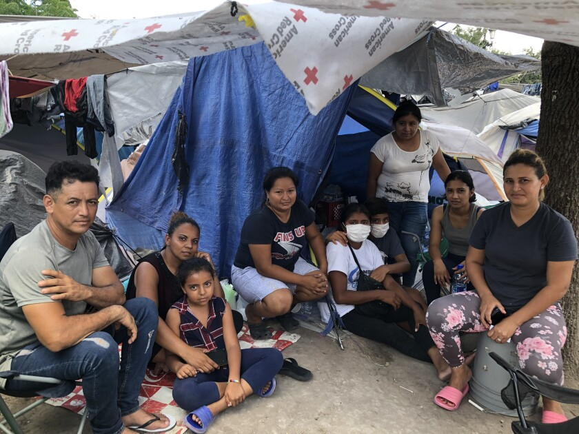 Neighbors at the Reynosa migrant camp include Honduran Lesly Pineda, far right, and Guatemalan Jose Torres, far left.