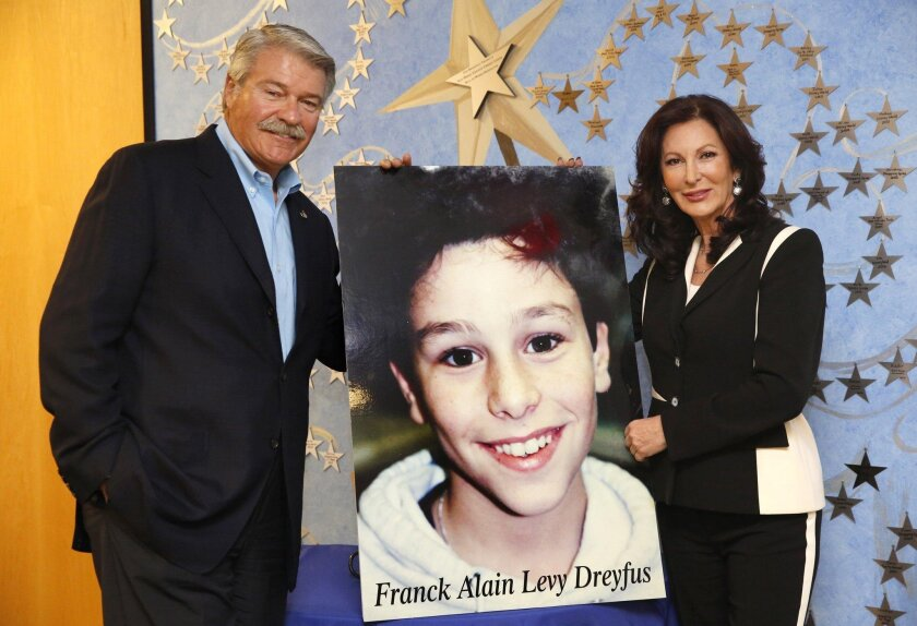 George and Hélène Gould at the offices of Make-A-Wish San Diego with a portrait of her late nephew, Franck Alain Levy Dreyfus. His premature death in 2001 inspired her to become a major donor to the organization.