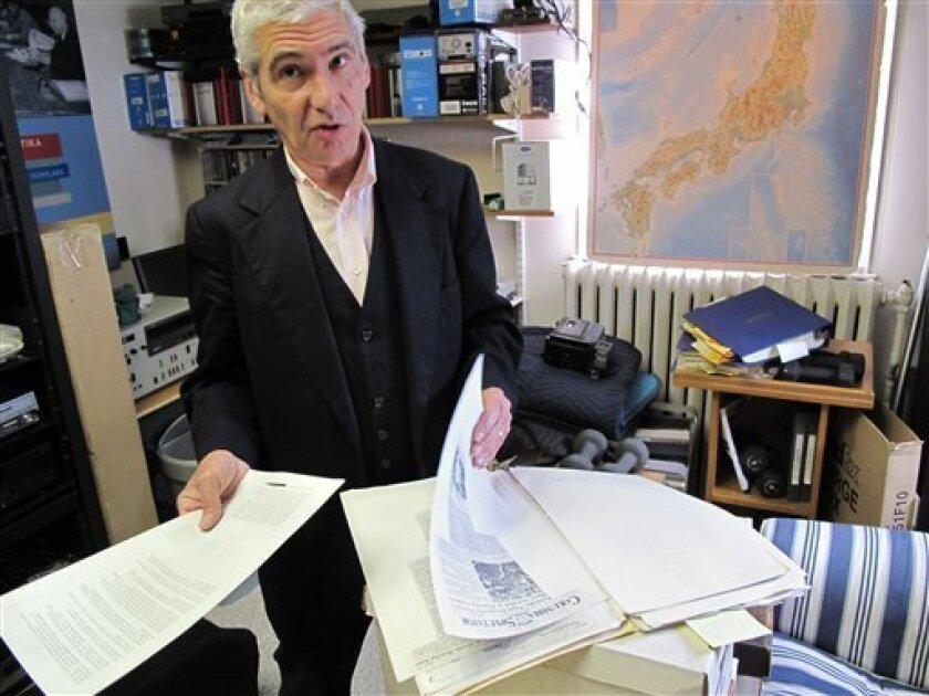 In this Oct. 21, 2011 photo, Joel Sucher goes through a file of documents related to secret New York Police Department program to monitor ethnic groups, student organizations and mosques, at his office in Hastings-on-Hudson, N.Y. (AP Photo/Chris Hawley)