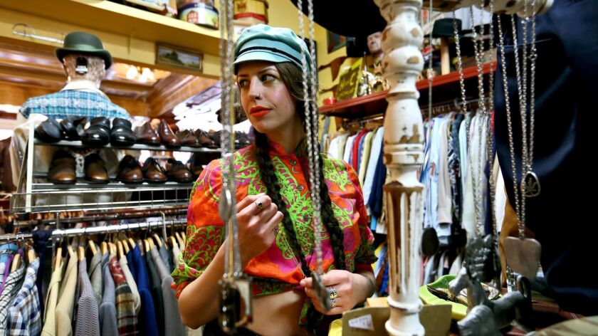 Sales person Shelby Hutchinson arranges the necklaces at Playclothes Vintage, at 3100 Magnolia, in B