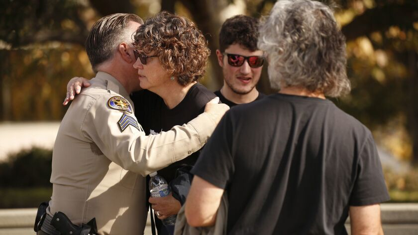 Susan Orfanos, the mother of Borderline shooting victim Telemachus Orfanos, hugs Ventura County Sheriff's Sergeant Eric Buschow, left, with 22-year-old son Tymaeus and husband Marc Orfanos, following the Ventura County Sheriff's Borderline shooting press conference.