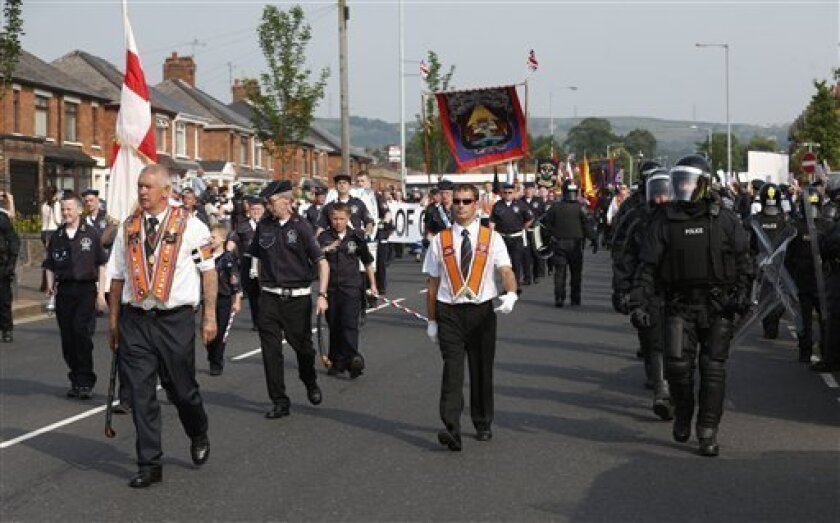 Riot police escort an Orange Order march past the Ardoyne area of North Belfast, Northern Ireland, Friday, July 12, 2013. A large security operation swung into place as a controversial Protestant Orange order march passed the Catholic Ardoyne area. (AP Photo/Peter Morrison)