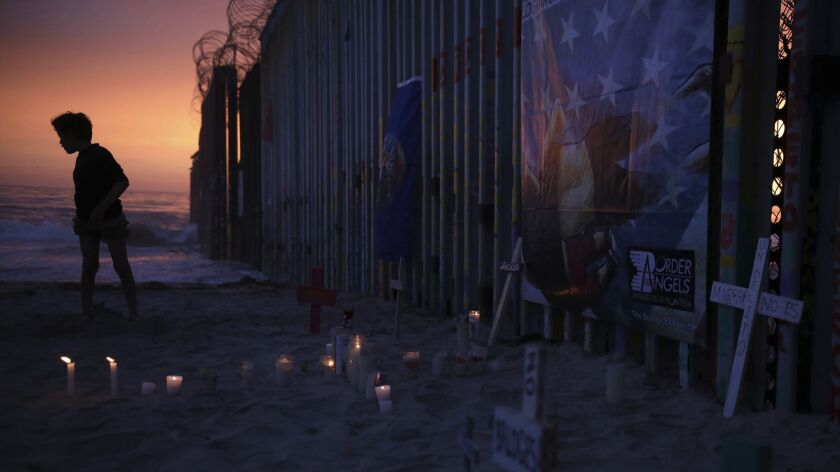 A youth stands by the border fence that separates Mexico from the United States, where candles and c
