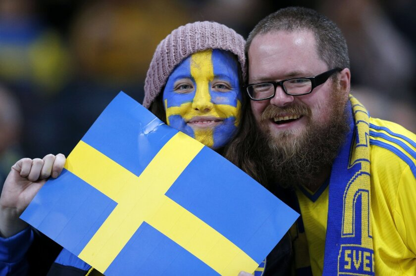 FILE - In this Tuesday, Nov. 19, 2013 file photo, Sweden fans pose with a Swedish flag before the World Cup qualifying soccer match between Sweden and Portugal in Stockholm, Sweden. For the first time since record-keeping began in 1749, Sweden now has more men than women. Swedes don't quite know wh