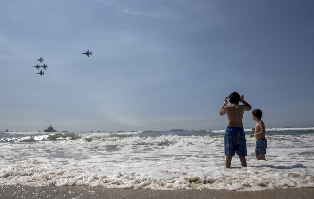 Ari Anival, 8, left, covers his ears as he and brother Uri, 7, right, watch the U.S. Air Force Thunderbirds