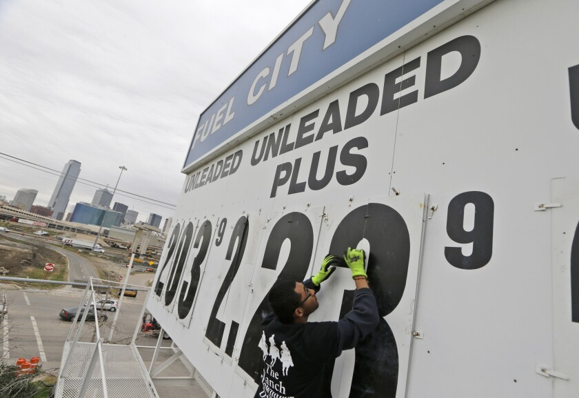 Luis Vargas changes the gas price sign at the Fuel City gas station in Dallas on Dec. 17. Falling gas prices have helped give consumers more spending money.