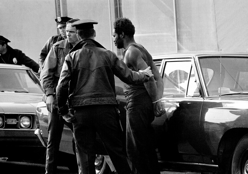 A Black Panther surrenders to police after a four-hour confrontation at the party headquarters in Los Angeles, Dec. 9, 1969.