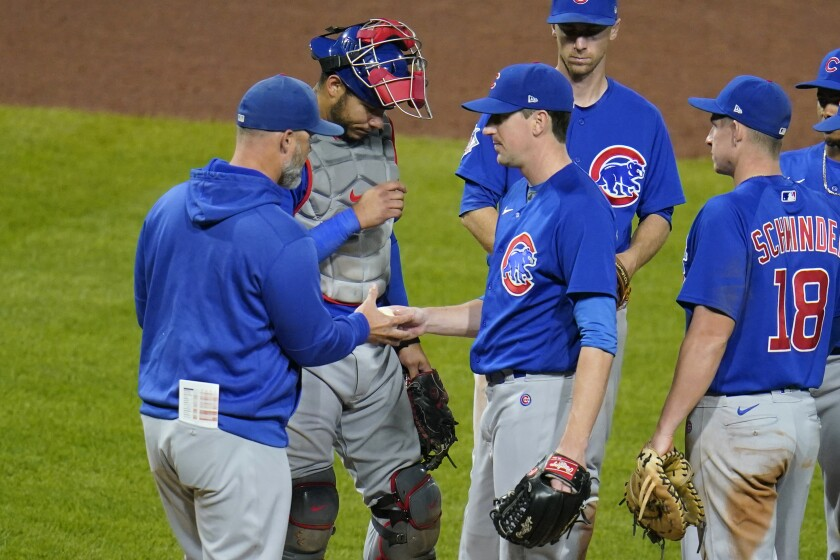 Chicago Cubs starting pitcher Kyle Hendricks, center, hands the ball to manager David Ross, left, as he leaves the baseball game in the sixth inning against the Pittsburgh Pirates in Pittsburgh, Wednesday, Sept. 29, 2021. (AP Photo/Gene J. Puskar)