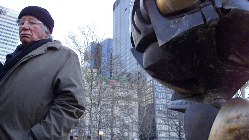 """German artist Fritz Koenig stands next to his bronze sculpture """"The Sphere"""" after a dedication ceremony in New York in 2002."""